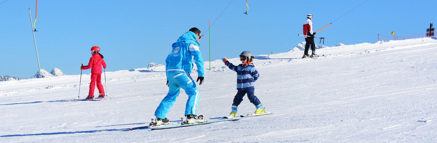 A ski instructor wearing a blue uniform and a young child on a ski lesson in the sun.