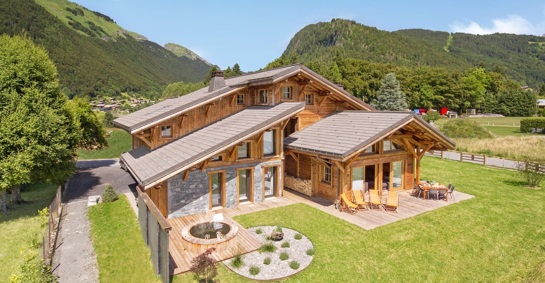 Morzine chalet with a hot tub and dining table in a sunny garden