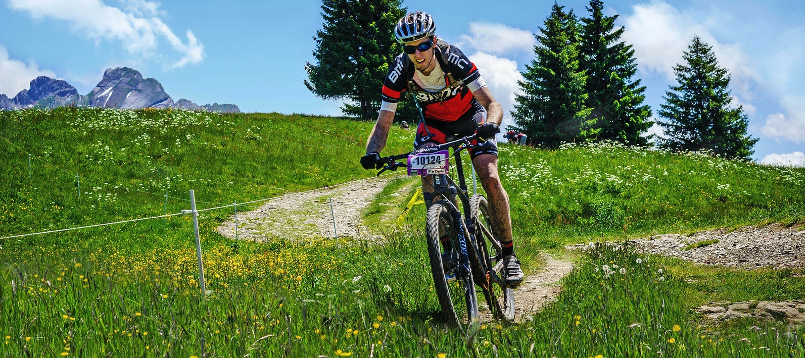 mountain biker riding down a single-track through an Alpine meadow