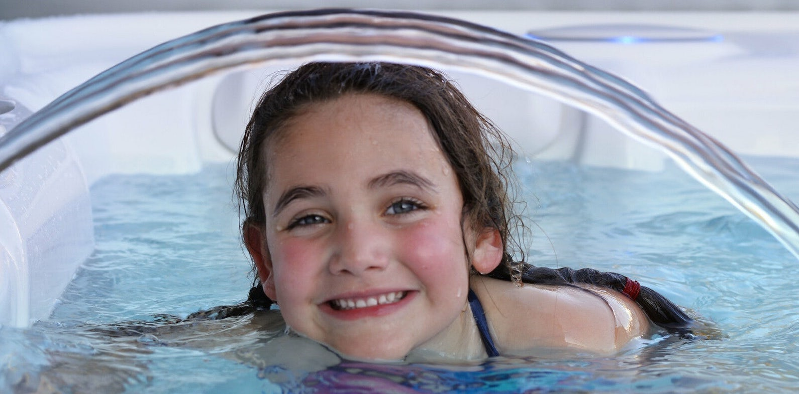 Smiling young girl in a hot tub with a water fountain going over her head.