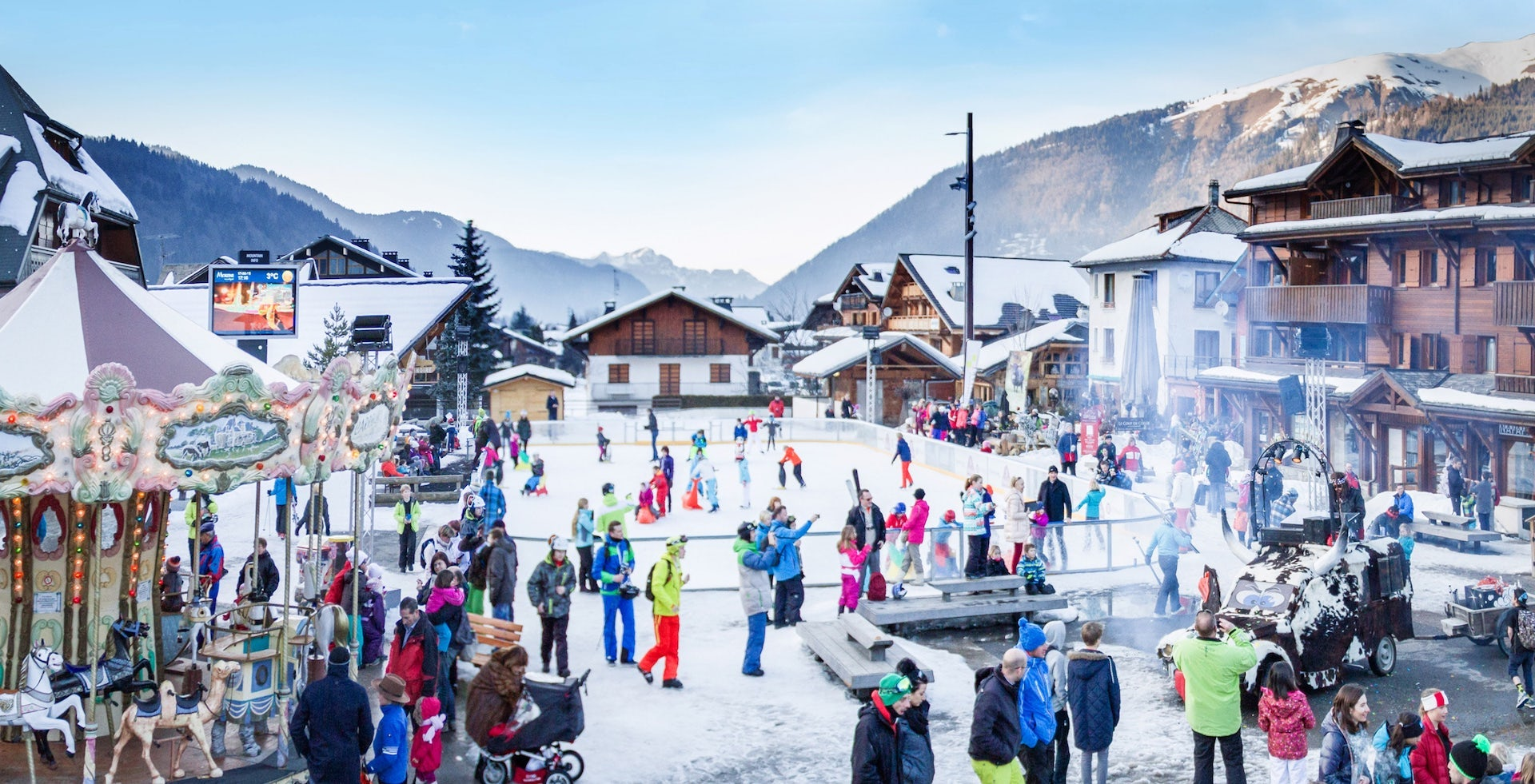 Families in a snowy square with an ice rink in the centre of the family friendly resort of Morzine in winter.